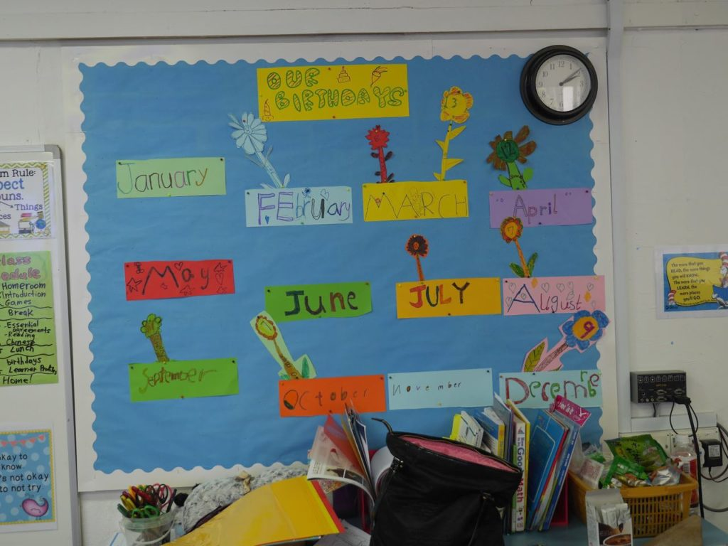 Decorating the class noticeboard with their handicrafts of birthday months
